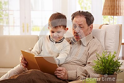 Grandfather reading book to grandson