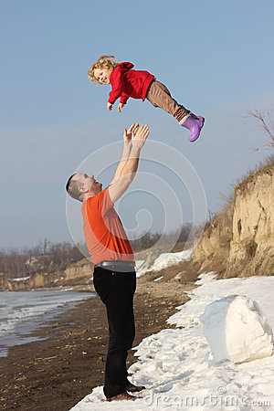 Grandfather throwing his granddauther in the air