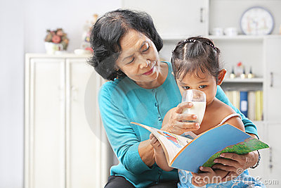 Grandma giving milk to her granddaugter