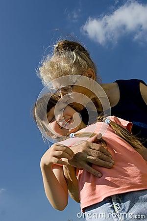 Grandma kissing her granddaughter