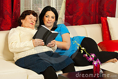 Grandma reading book to granddaughter
