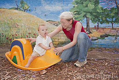 Grandmother and baby playing and having fun on toy