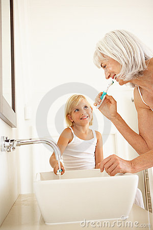 Grandmother Brushing Teeth With Granddaughter