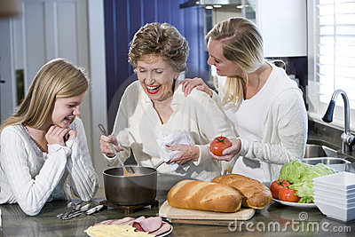 Grandmother with family cooking in kitchen