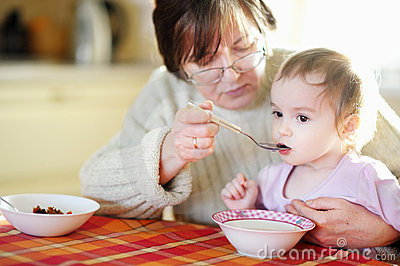 Grandmother feeding her little baby granddaughter