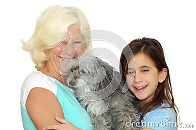 Grandmother and girl hugging the family dog