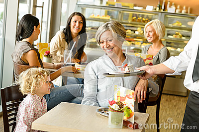 Grandmother and grandchild waiting cake order cafe