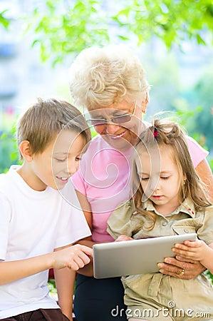 Grandmother with grandchildren using tablet