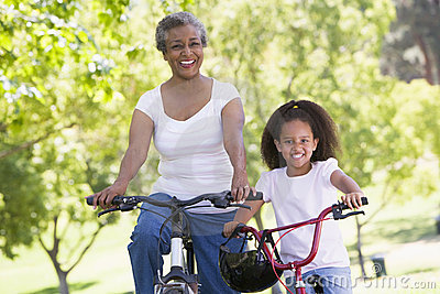 Grandmother and granddaughter on bikes outdoors