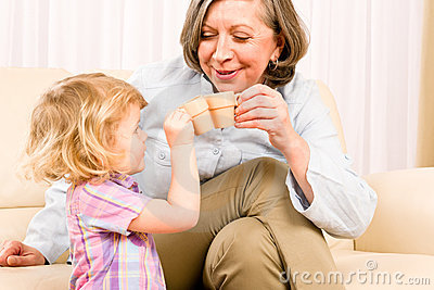 Grandmother with granddaughter drink tiny cups
