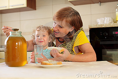Grandmother with the granddaughter eating honey