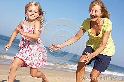 Grandmother And Granddaughter Running Along Beach