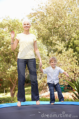 Grandmother And Grandson Jumping On Trampoline In