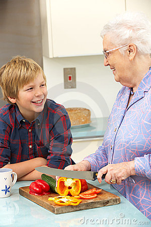 Grandmother and grandson preparing food in kitchen