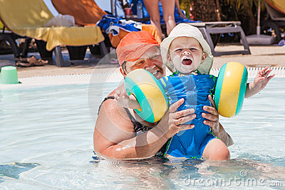 Grandmother and grandson swimming together in the pool