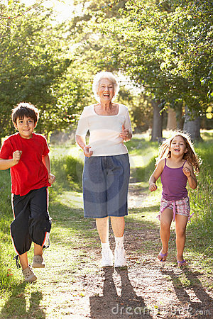 Grandmother Jogging In Park With Grandchildren