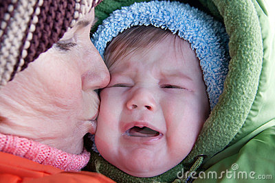 Grandmother kissing crying baby.