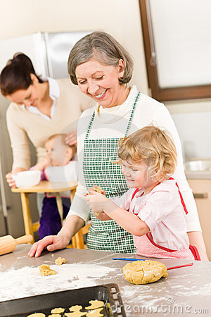 Grandmother with little girl prepare dough
