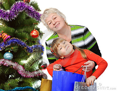 Grandmother and little near Christmas tree.