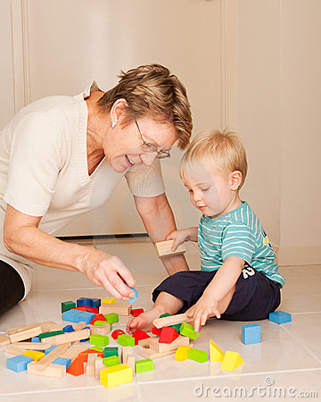A grandmother or nanny plays with a little boy