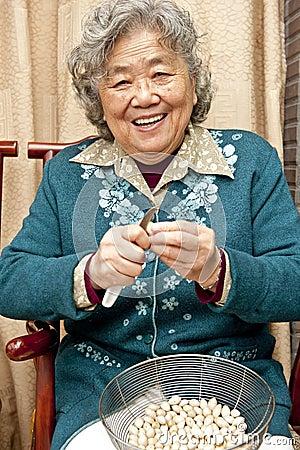 Grandmother peeling nut fruit
