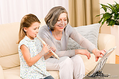 Grandmother teach young girl play flute happy