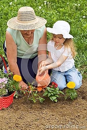 Grandmother teaching child the basics of gardening