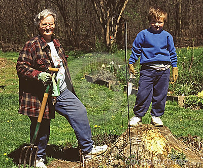 Grandmother teaching grandson lawn work