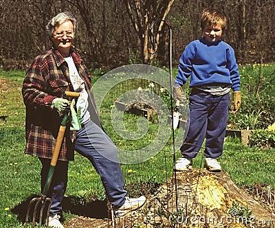 Grandmother teaching grandson lawn work