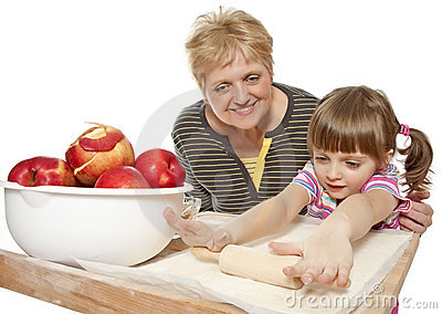 grandmother teaching her granddaughter bake