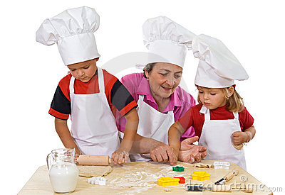 Grandmother teaching kids making cookies