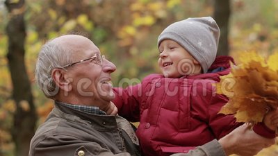 Grandpa with toddler boy resting in autumn park stock video footage