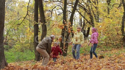 Grandparents and children with leaves in autumn stock video