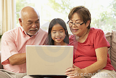 Grandparents And Grandaughter Using Laptop Compute