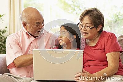 Grandparents And Grandaughter Using Laptop Compute