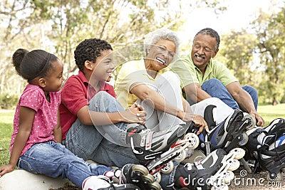 Grandparents With Grandchildren Putting On Skates