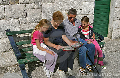 Grandparents with grandchildren watch a photo