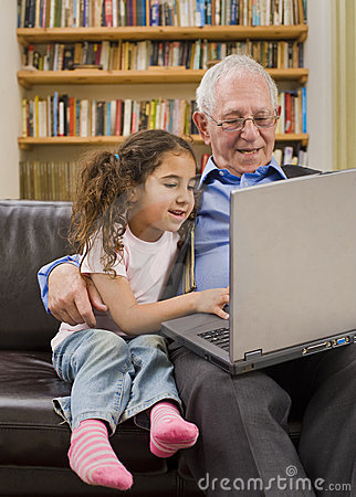 Grandparents and granddaughter with computer