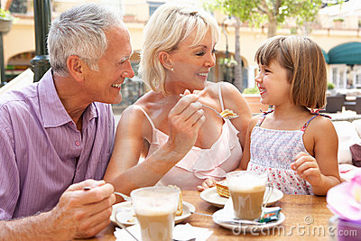 Grandparents With Granddaughter Enjoying Coffee