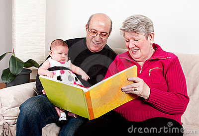 Grandparents reading book to baby girl