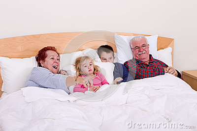 Grandparents Watching TV in the bed with their Grand kids