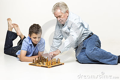 Grandson and grandfather play chess