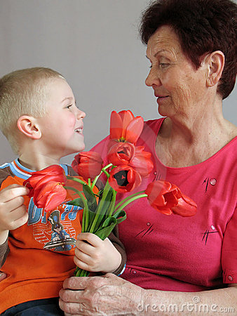 Grandson present flowers to grandmother