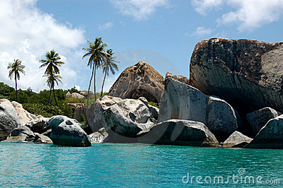 Granite boudlers and palm trees line turquoise waters