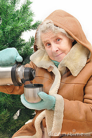 Granny with hot tea under fir