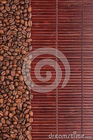 Granos de café que mienten en una estera de bambú