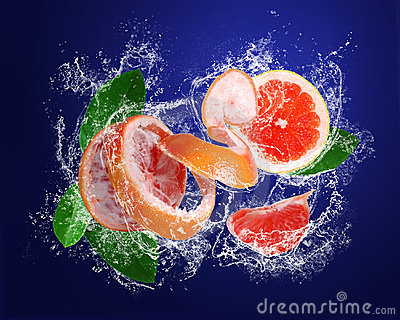 Grapefruit with pieces and leaves in water drops