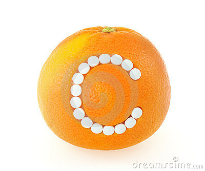 Grapefruit with vitamin c pills over white backgro