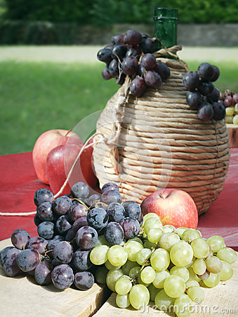 Grapes apples and tank of wine