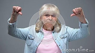 Grappig bejaard wijfje die duim-onderaan gebaar, ongelukkig met de overheid van de staat tonen stock footage